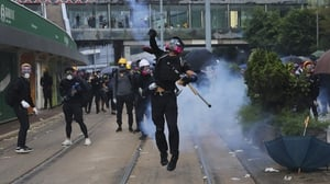 An anti-government protester throws a tear gas canister back at police during a protest in Hong Kong