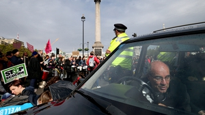 An Extinction Rebellion protester locks himself to the steering wheel of a hearse at the roundabout in Trafalgar Square, in Westminster, London