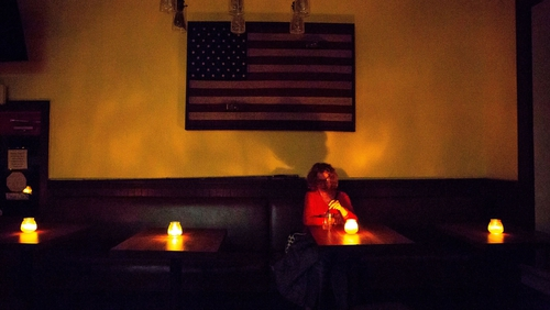 A local sits in a candle-lit restaurant in Sonoma, California, during the planned power outage