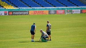 Joe Schmidt, left, IRFU head of operations Ger Carmody and scrum coach Greg Feek examine the playing surface at Hakatanomori Stadium