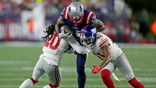 Josh Gordon  of the New England Patriots is hit by Janoris Jenkins, left, of the New York Giants and Antoine Bethea