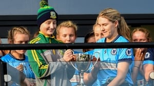 Simonstown captain Ailbhe McHugh receives the county title from Meath U-16 player Aoife Hughes, who is currently battling cancer.