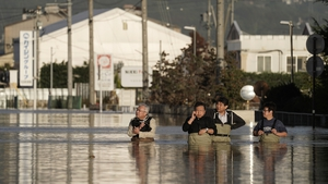 A group of men wearing chest-high waders check the condition of their office in a typhoon Hagibis flooded street in Nagano