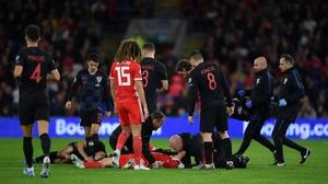 Daniel James receives medical attention after an aerial clash with Croatian defender Domagoj Vida