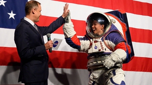 Advance space suit engineer Kristine Davis (R) is welcomed to the stage during a press conference displaying the next generation of spacesuits
