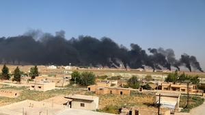 Smoke clouds rising from scene of clashes between the SDF and Turkish troops in northeastern Syria