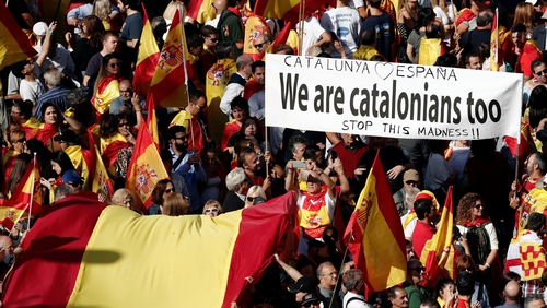 Around 80,000 people, according to a police estimate, marched down Barcelona's central Gracia thoroughfare waving Spanish and Catalan flags