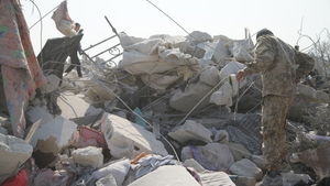 People walk among the rubble on the compound where Abu Bakr al-Baghdadi is believed to have died