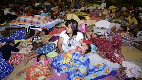 Villagers take shelter in a temporary evacuation centre in Digos City
