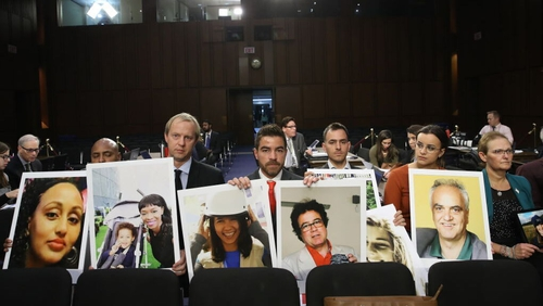 Families of those who died aboard Ethiopian Airlines Flight 302 sit with pictures of their loved ones during the hearing