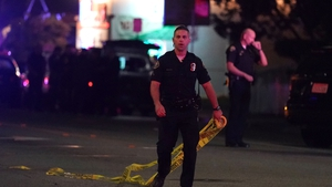 Police close off the scene of a shooting that left three people dead