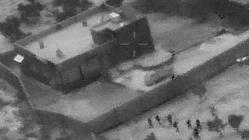 The grainy image shows troops advancing on the compound of IS leader Abu Bakr al-Baghdadi