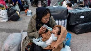A woman feeds her baby after their arrival from the island of Lesbos to the port of Piraeus near Athens in early October