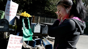 A woman reads sympathy messages for the victims who died at an Airbnb rental house in Orinda, California last week