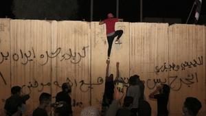 A protester attempts to climb the wall outside the Iranian consulate in Kerbala