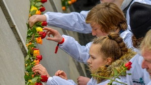 People place flowers at the Wall Memorial for the 30th anniversary of the fall of the Berlin Wall