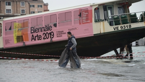 A man wears plastic bags on his feet to keep the water out as he walks past a ferry stranded on the docks