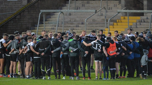 Kilcoo players huddle together after their win against Derrygonnelly