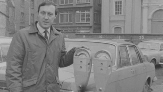 RTÉ reporter Tom McCaughren at parking meters, Dublin city centre (1969)