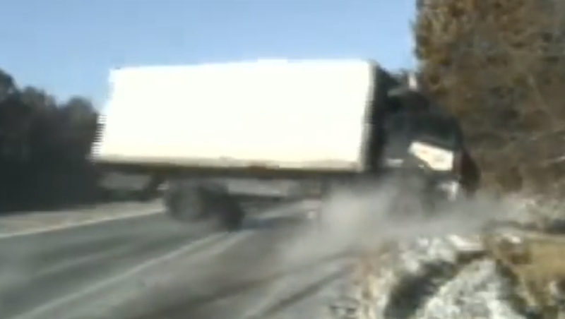 Close call as truck topples near troopers changing tyre