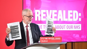 Jeremy Corbyn holds a redacted copy of the Department for International Trade's UK-US Trade and Investment Working Group