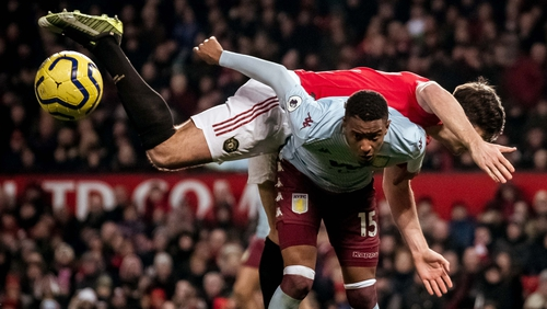 Harry Maguire battles for possession against Aston Villa