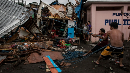 Villagers working among damaged houses in the aftermath of Typhoon Kammuri