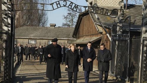 Angela Merkel began the visit by walking through a gate bearing the chilling Nazi message 'Arbeit macht frei'