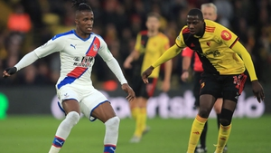 Wilfriend Zaha is challenged by Abdoulaye Doucoure