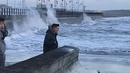 Passers-by watch on as high winds arrive at Tramore in Waterford