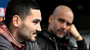 Manchester City head coach Pep Guardiola (R) looks on as Ilkay Gundogan speaks to the press