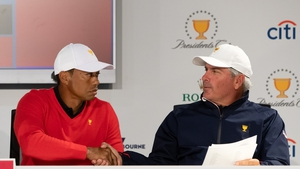 Playing Captain Tiger Woods of the United States team shakes hands with his assistant captain Fred Couples