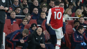 Per Mertesacker and Freddie Ljungberg look on as Mesut Ozil kicks his gloves in the air after he is subbed