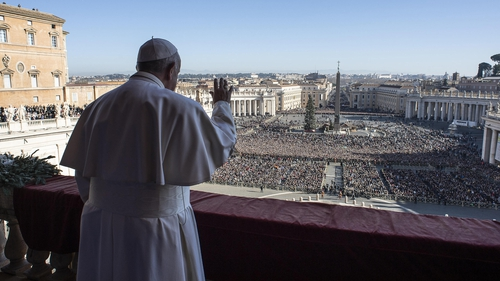 "Pope Francis waves from the balcony of St Peter's basilica during the traditional ""Urbi et Orbi"" Christmas message"
