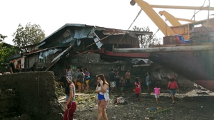 Villagers walk around a cargo ship washed ashore on Christmas Day in the typhoon-hit city of Ormoc
