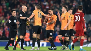 Conor Coady (16) and other Wolves players argue with referee Anthony Taylor