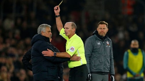 Southampton manager Ralph Hasenhuttl (R) looks on as referee Mike Dean shows Jose Mourinho (L) a yellow card