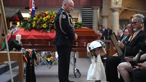 Charlotte O'Dwyer wears her father's helmet during his funeral service