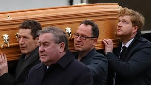Marian Finucane's son Jack looks skyward as her coffin is carried into the church in Co Kildare