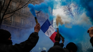 Protesters burn blue flares and wave a French flag during a demonstration in Paris