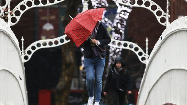 A man battles wind and rain while crossing the Ha'penny Bridge in Dublin (Photos: Rolling News)