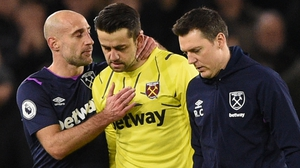 Lukasz Fabianski (centre) leaves the pitch injured against Sheffield United