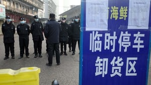 Security guards stand in front of a seafood market, where a man who died from virus had purchased goods from