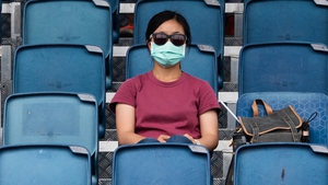 A masked woman watches an Australian Open practice session in Melbourne
