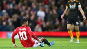 Manchester United's Marcus Rashford lies on the pitch in pain after picking up a back injury