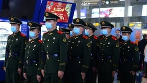 Chinese police officers wearing masks patrol the Hongqiao Railway Station in Shanghai