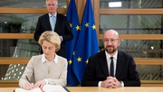 Ursula von der Leyen signs the agreement as Michel Barnier and Charles Michel look on (Pic: @vonderleyen)
