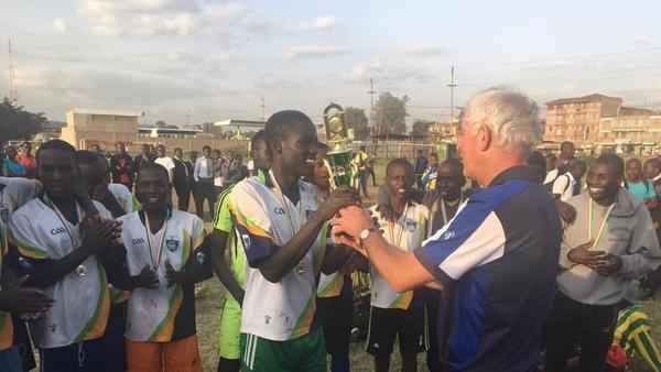 Kerryman Eddie Sheehy (R) presents the 'Eddie Sheehy Cup' to the winners of a soccer tournament in Embulbul, Kenya