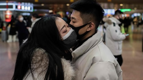 A couple wearing protective masks embrace at a Beijing railway station