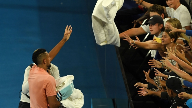 Kyrgios throws a towel to his fans after victory